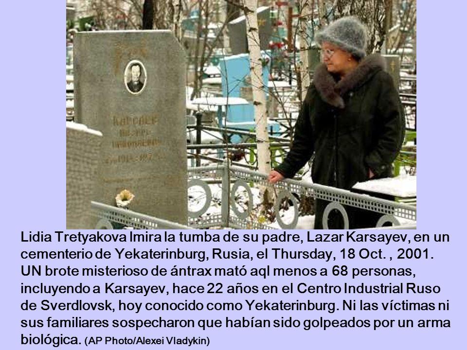 Lidia Tretyakova lmira la tumba de su padre, Lazar Karsayev, en un cementerio de Yekaterinburg, Rusia, el Thursday, 18 Oct., 2001. UN brote misterioso