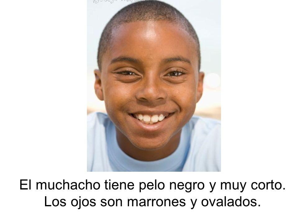 El muchacho tiene pelo negro y muy corto. Los ojos son marrones y ovalados.