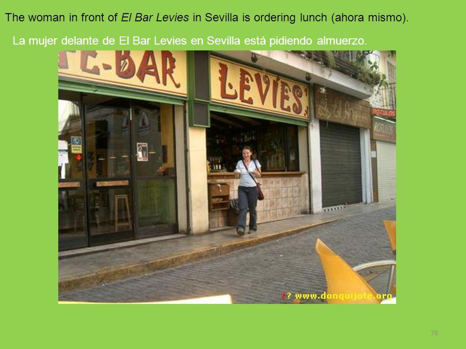 76 The woman in front of El Bar Levies in Sevilla is ordering lunch (ahora mismo). La mujer delante de El Bar Levies en Sevilla está pidiendo almuerzo