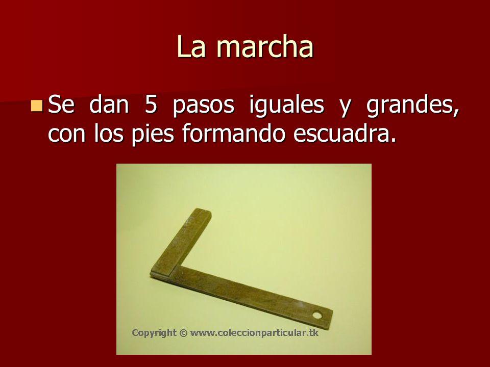 La marcha Se dan 5 pasos iguales y grandes, con los pies formando escuadra. Se dan 5 pasos iguales y grandes, con los pies formando escuadra.