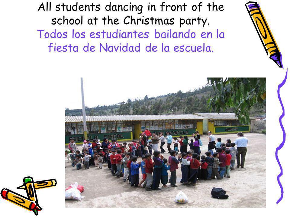 All students dancing in front of the school at the Christmas party. Todos los estudiantes bailando en la fiesta de Navidad de la escuela.