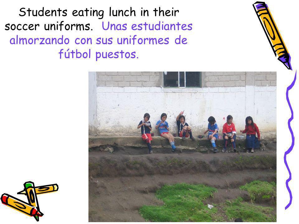 Students eating lunch in their soccer uniforms. Unas estudiantes almorzando con sus uniformes de fútbol puestos.