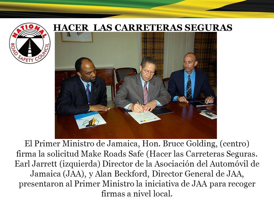 El Primer Ministro de Jamaica, Hon. Bruce Golding, (centro) firma la solicitud Make Roads Safe (Hacer las Carreteras Seguras. Earl Jarrett (izquierda)