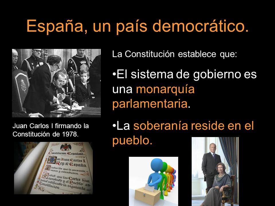 España, un país democrático. Juan Carlos I firmando la Constitución de 1978. La Constitución establece que: El sistema de gobierno es una monarquía pa