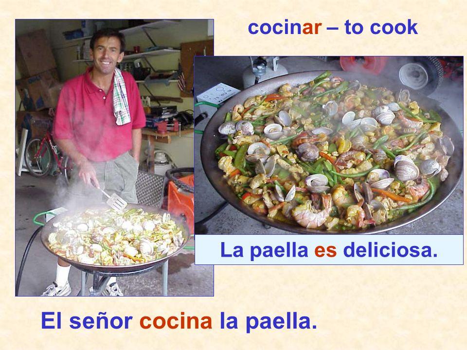 El señor cocina la paella. La paella es deliciosa. cocinar – to cook