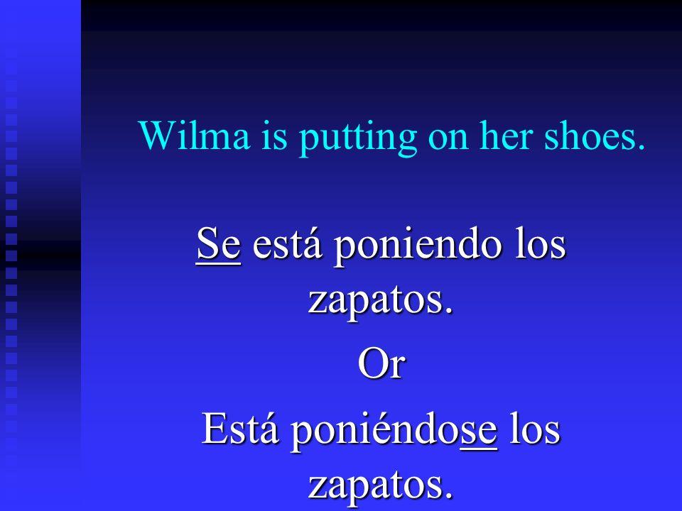 Wilma is putting on her shoes. Se está poniendo los zapatos. Or Está poniéndose los zapatos.