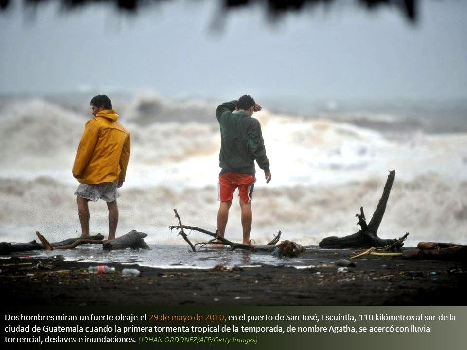Dos hombres miran un fuerte oleaje el 29 de mayo de 2010, en el puerto de San José, Escuintla, 110 kilómetros al sur de la ciudad de Guatemala cuando la primera tormenta tropical de la temporada, de nombre Agatha, se acercó con lluvia torrencial, deslaves e inundaciones.