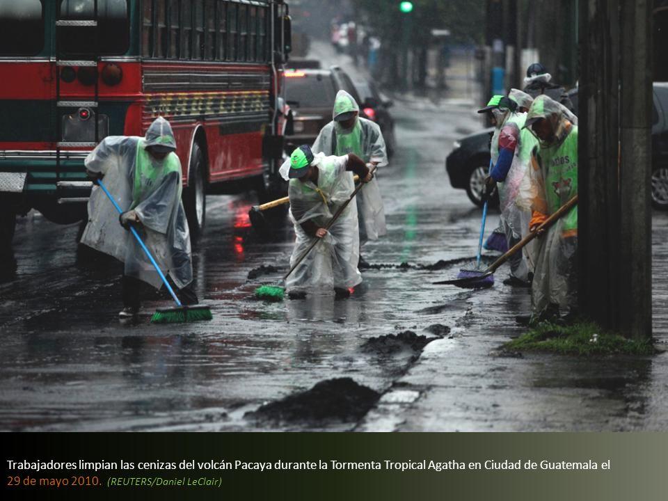 Trabajadores limpian las cenizas del volcán Pacaya durante la Tormenta Tropical Agatha en Ciudad de Guatemala el 29 de mayo 2010.