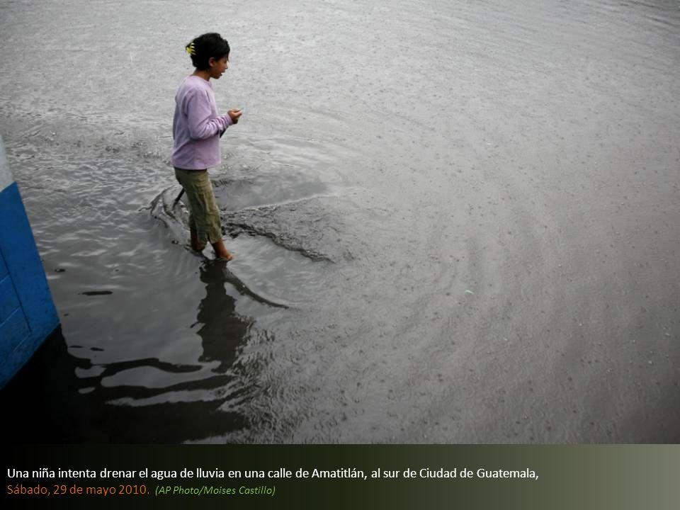 Una niña intenta drenar el agua de lluvia en una calle de Amatitlán, al sur de Ciudad de Guatemala, Sábado, 29 de mayo 2010.