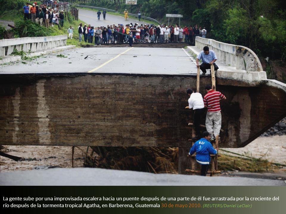 La gente observa el río Madre Vieja, crecido a causa de las fuertes lluvias causadas por la tormenta tropical Agatha en Patulul, Guatemala, Sábado, 29