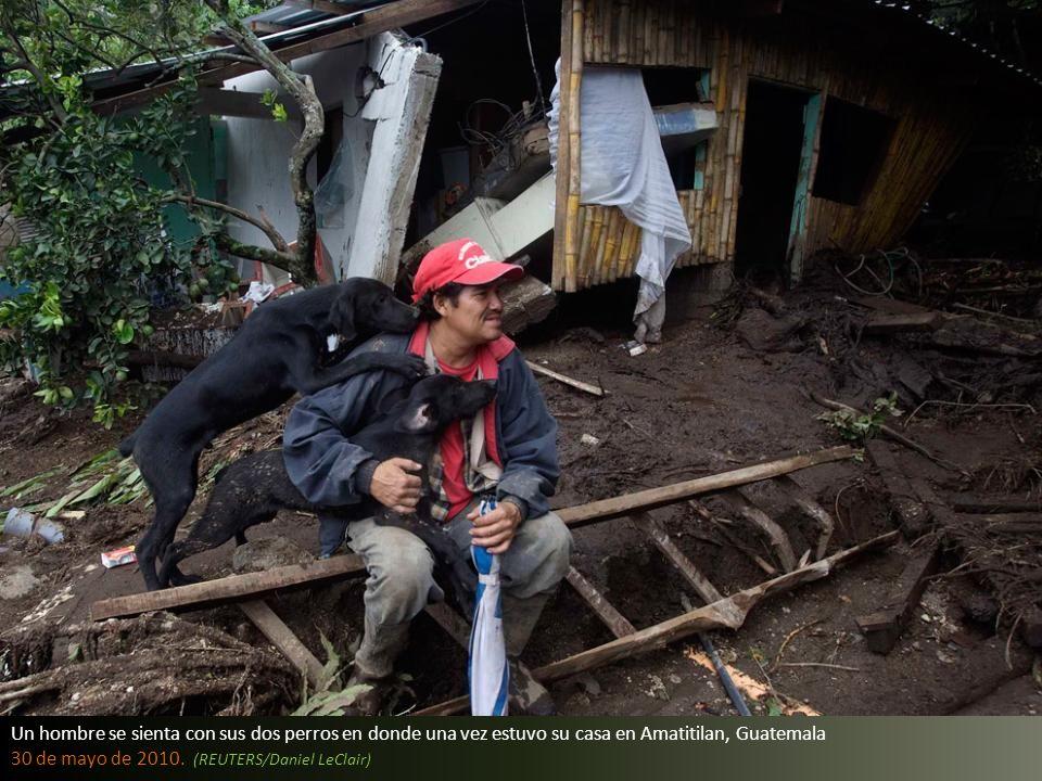 Un hombre se sienta con sus dos perros en donde una vez estuvo su casa en Amatitilan, Guatemala 30 de mayo de 2010.