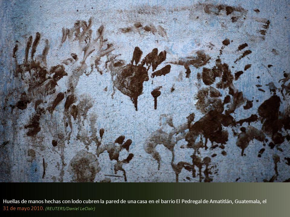 Huellas de manos hechas con lodo cubren la pared de una casa en el barrio El Pedregal de Amatitlán, Guatemala, el 31 de mayo 2010.