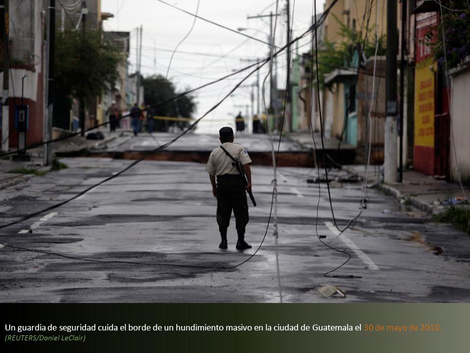 Un guardia de seguridad cuida el borde de un hundimiento masivo en la ciudad de Guatemala el 30 de mayo de 2010.