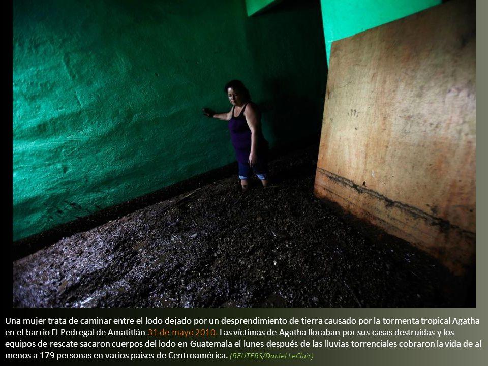 Una mujer trata de caminar entre el lodo dejado por un desprendimiento de tierra causado por la tormenta tropical Agatha en el barrio El Pedregal de Amatitlán 31 de mayo 2010.