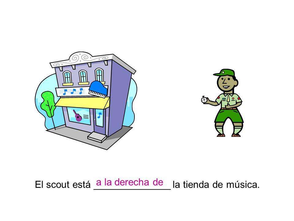 El scout está ______________ la tienda de música. a la derecha de