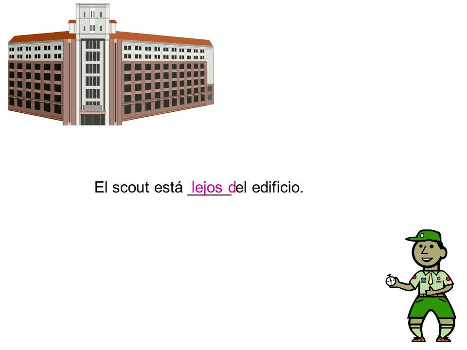 El scout está _____ el edificio.lejos d