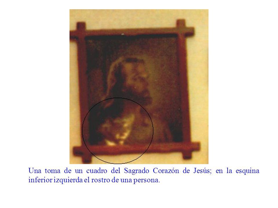 Una toma de un cuadro del Sagrado Corazón de Jesús; en la esquina inferior izquierda el rostro de una persona.