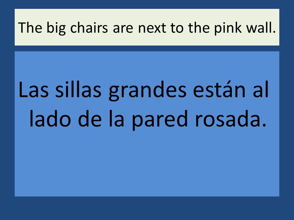 The big chairs are next to the pink wall. Las sillas grandes están al lado de la pared rosada.