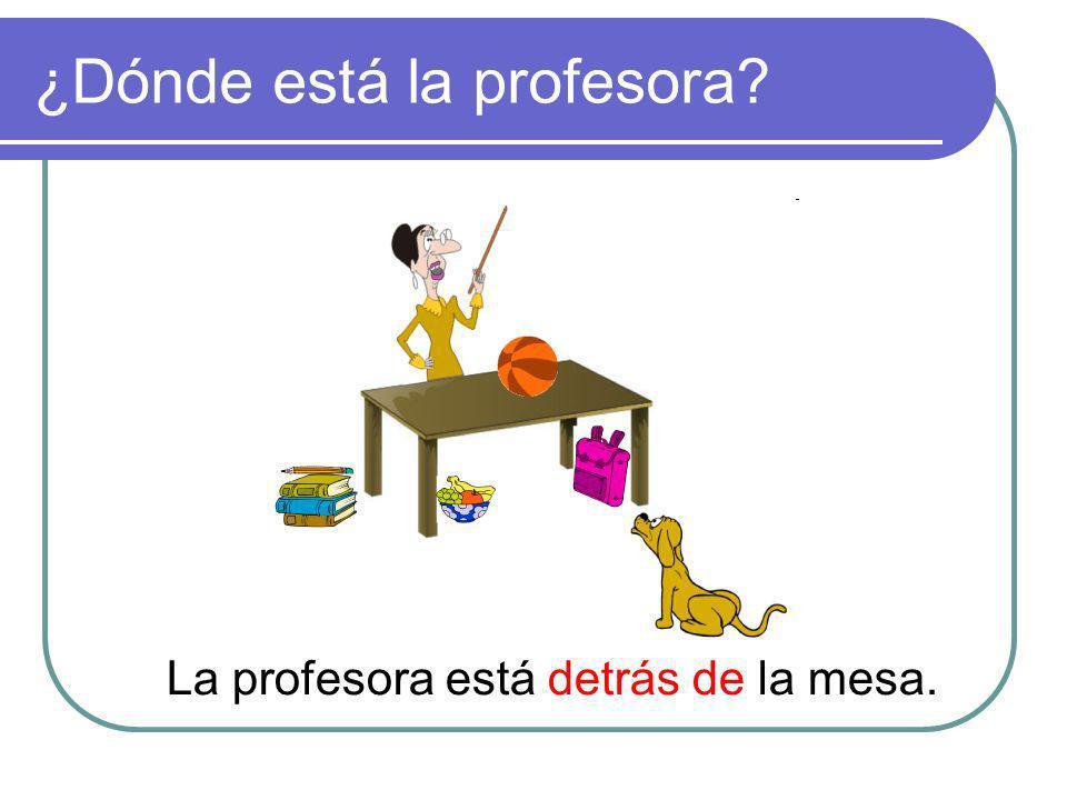 ¿Dónde está la profesora? La profesora está detrás de la mesa.