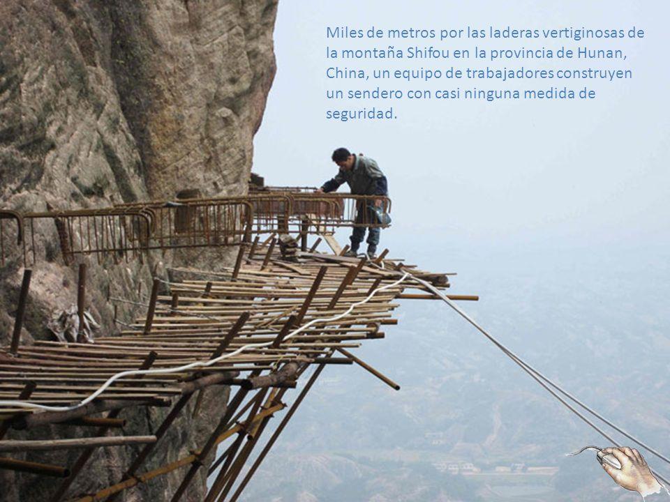 Miles de metros por las laderas vertiginosas de la montaña Shifou en la provincia de Hunan, China, un equipo de trabajadores construyen un sendero con casi ninguna medida de seguridad.