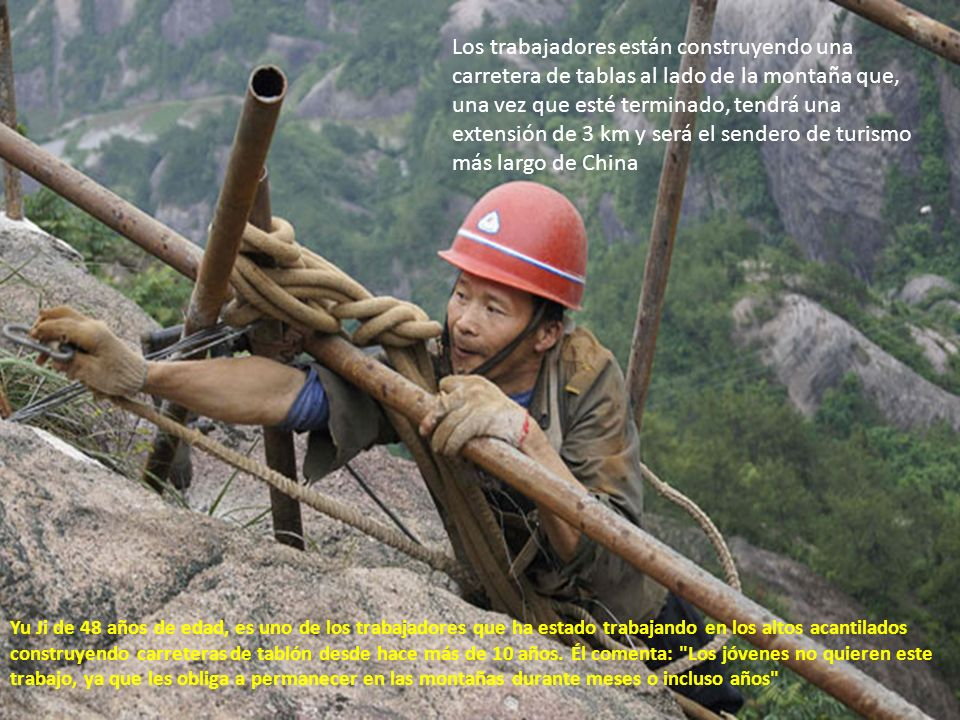 Los trabajadores están construyendo una carretera de tablas al lado de la montaña que, una vez que esté terminado, tendrá una extensión de 3 km y será el sendero de turismo más largo de China Yu Ji de 48 años de edad, es uno de los trabajadores que ha estado trabajando en los altos acantilados construyendo carreteras de tablón desde hace más de 10 años.