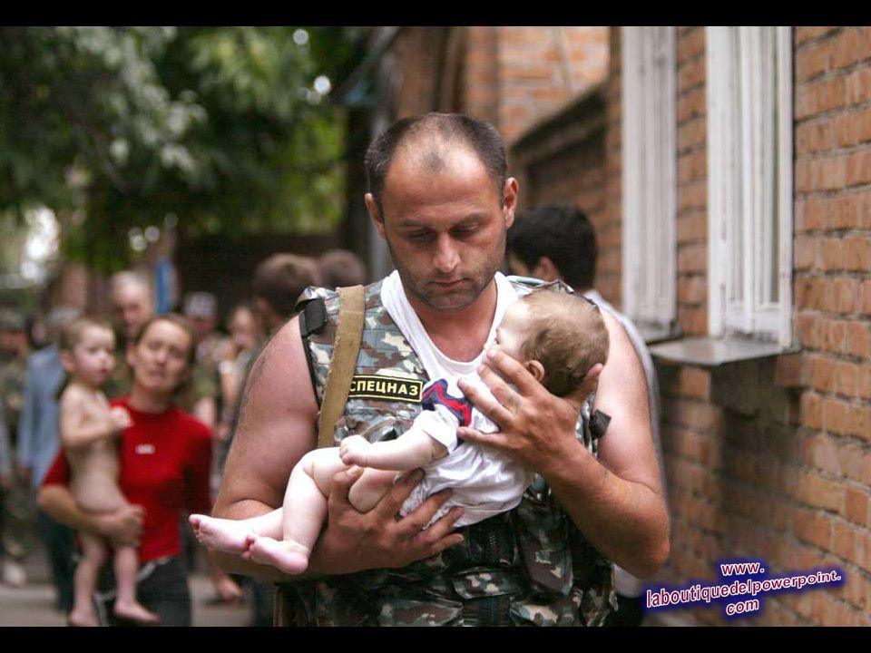 Un oficial de policía de Rusia lleva a un bebé liberado de la escuela que había sido tomada por secuestradores en la ciudad de Beslan, en la provincia