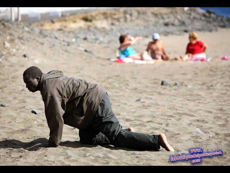 Un inmigrante ilegal se arrastra frente a bañistas después de su llegada, en la playa de Gran Tarajal, en España, Islas Canarias 5 de mayo 2006. Unos