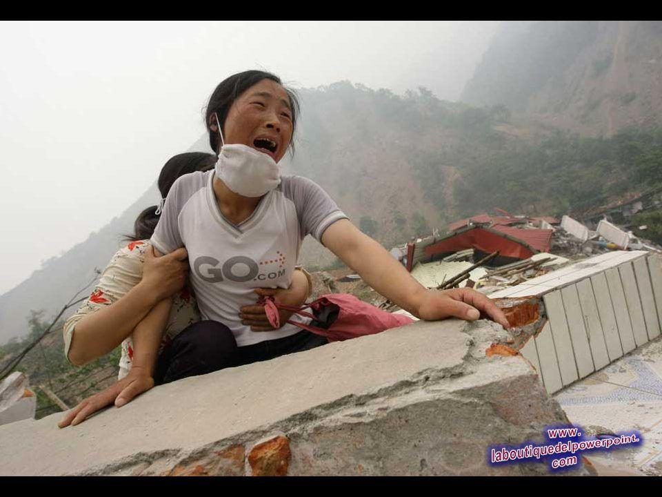 Una mujer llora mientras no puede encontrar a su hija y esposo en la parte superior de las ruinas de una escuela destruida por terremoto que golpeó el