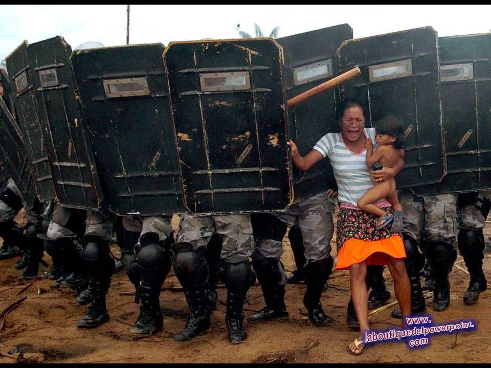 Una mujer sostiene a su hijo al tratar de resistir el avance de los policías del estado Amazonas, que tenían la orden de expulsar a la mujer y otros 2