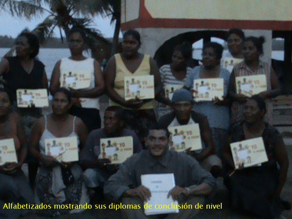 Alfabetizados mostrando sus diplomas de conclusión de nivel