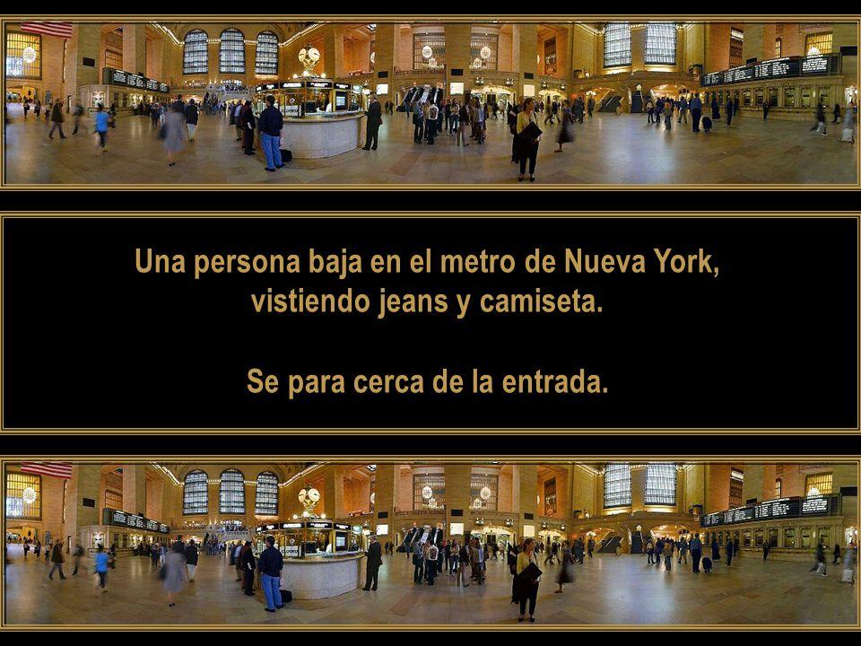 Una persona baja en el metro de Nueva York, vistiendo jeans y camiseta.