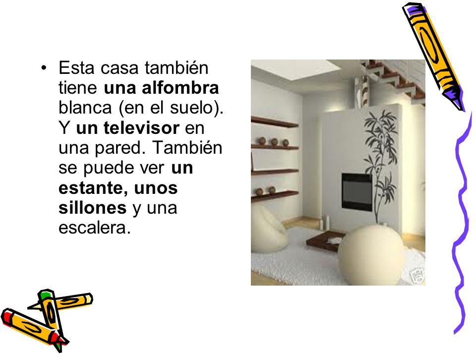 Esta casa también tiene una alfombra blanca (en el suelo). Y un televisor en una pared. También se puede ver un estante, unos sillones y una escalera.