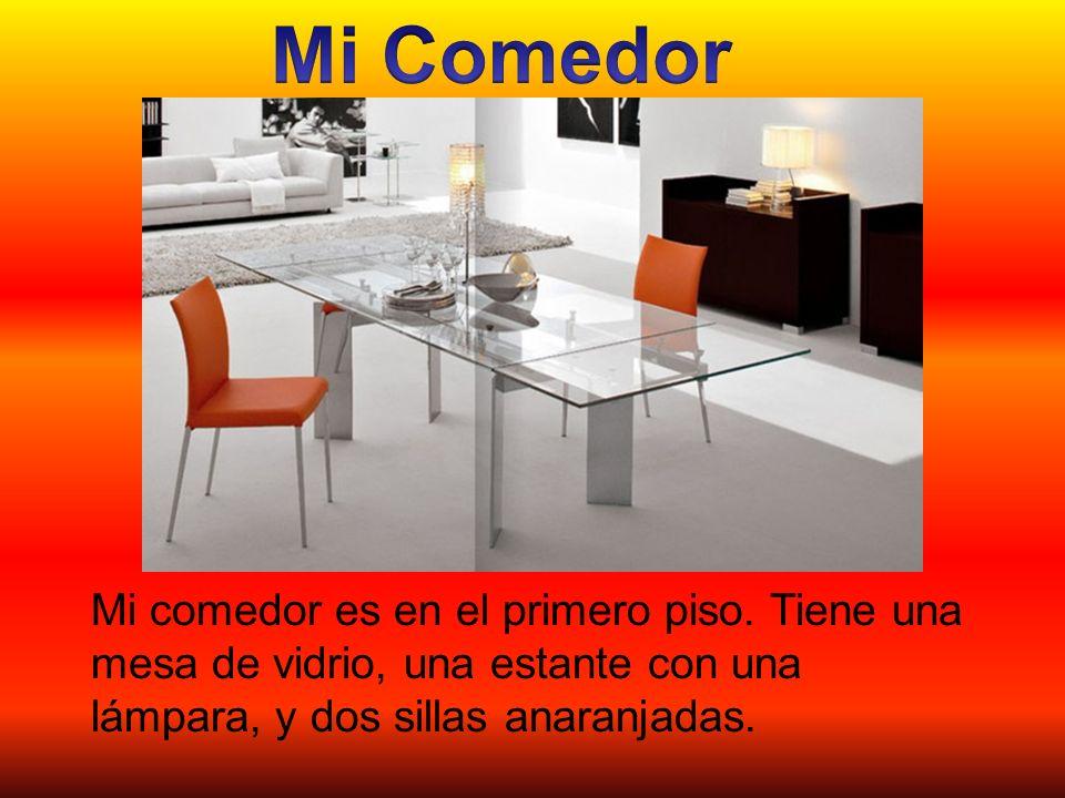 Mi comedor es en el primero piso. Tiene una mesa de vidrio, una estante con una lámpara, y dos sillas anaranjadas.