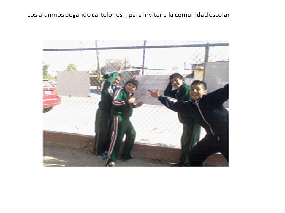 Los alumnos pegando cartelones, para invitar a la comunidad escolar