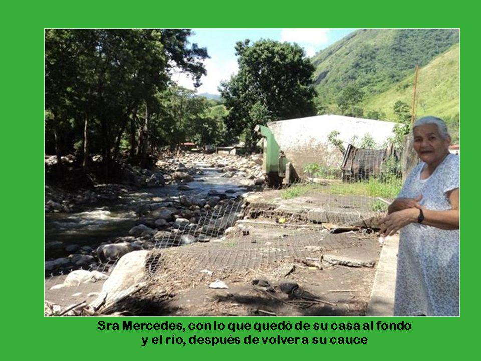 Sra Mercedes, con lo que quedó de su casa al fondo y el río, después de volver a su cauce