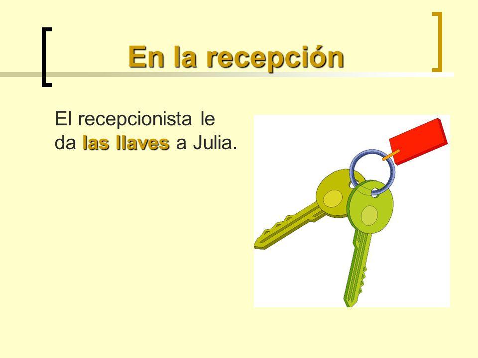 En la recepción las llaves El recepcionista le da las llaves a Julia.