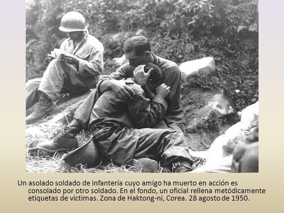 Un asolado soldado de infantería cuyo amigo ha muerto en acción es consolado por otro soldado. En el fondo, un oficial rellena metódicamente etiquetas