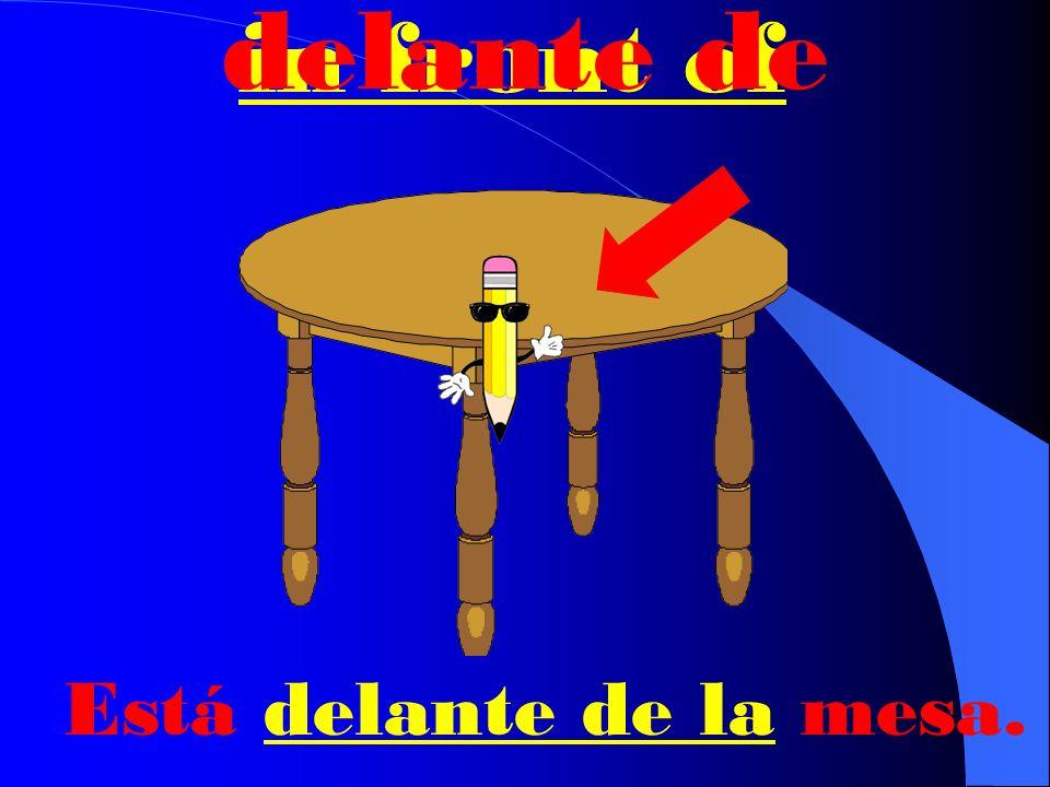 behind detrás de Está detrás de la mesa.