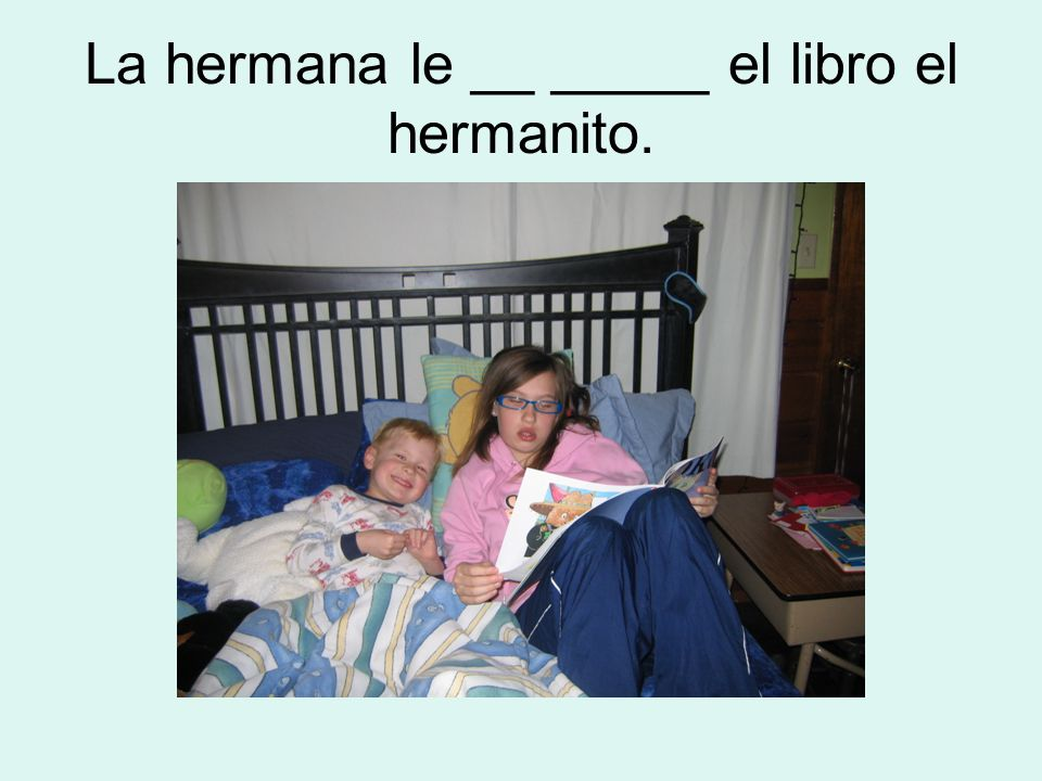 La hermana le __ _____ el libro el hermanito.