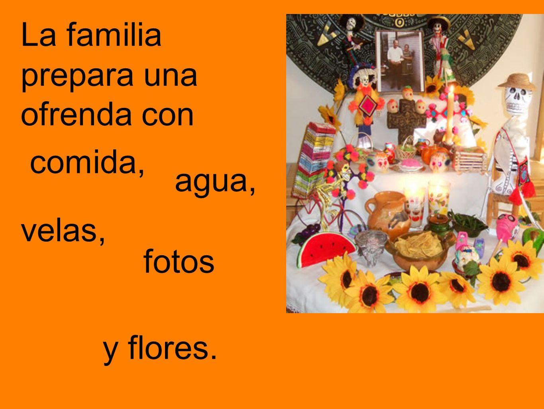La familia prepara una ofrenda con comida, agua, velas, fotos y flores.