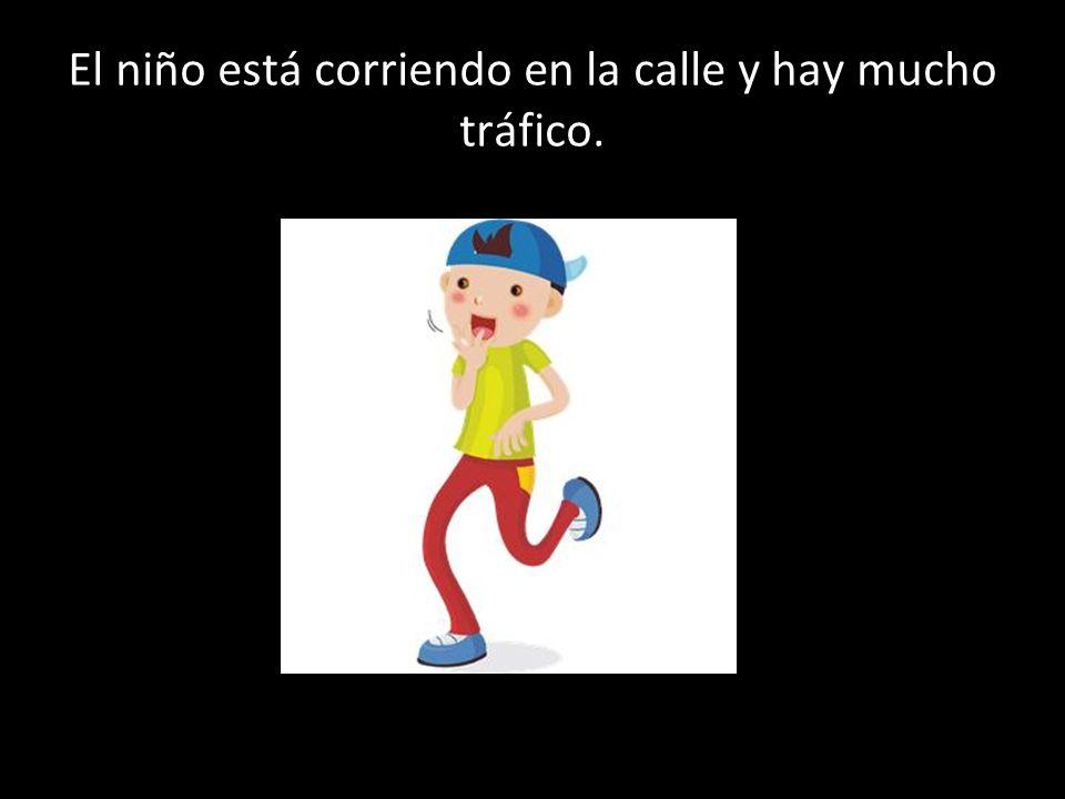 El niño está corriendo en la calle y hay mucho tráfico.