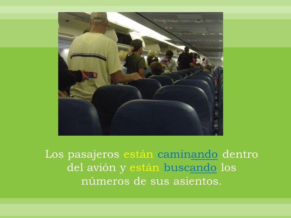Los pasajeros están caminando dentro del avión y están buscando los números de sus asientos.