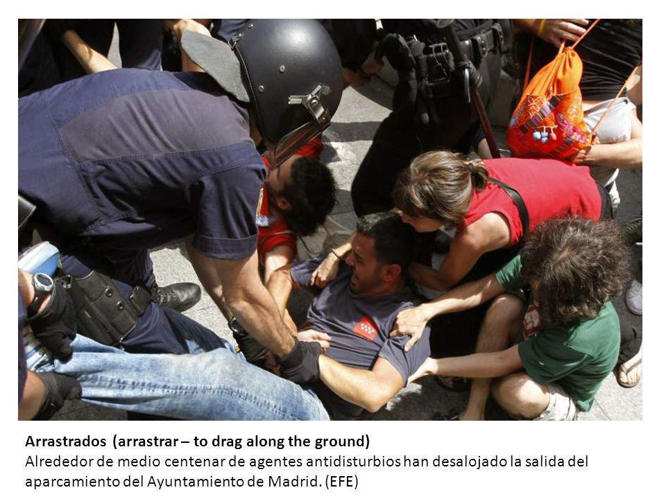 Arrastrados (arrastrar – to drag along the ground) Alrededor de medio centenar de agentes antidisturbios han desalojado la salida del aparcamiento del Ayuntamiento de Madrid.