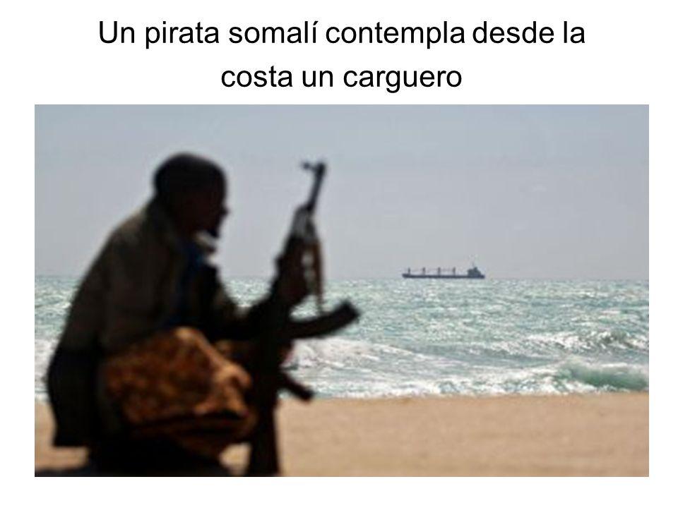 Un pirata somalí contempla desde la costa un carguero