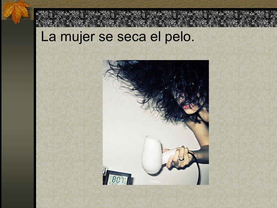 La mujer se seca el pelo.