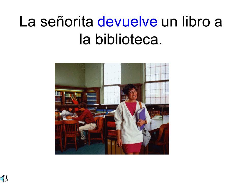 La señorita devuelve un libro a la biblioteca.