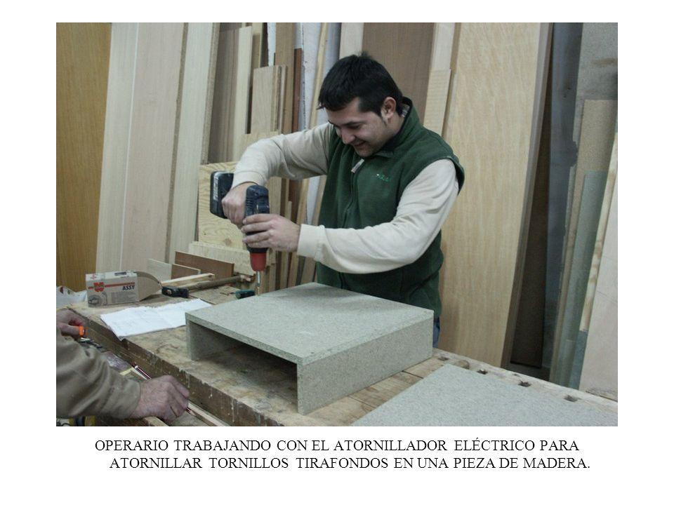 OPERARIO TRABAJANDO CON EL ATORNILLADOR ELÉCTRICO PARA ATORNILLAR TORNILLOS TIRAFONDOS EN UNA PIEZA DE MADERA.