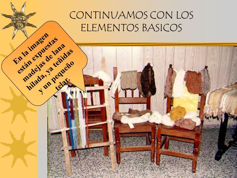 CONTINUAMOS CON LOS ELEMENTOS BASICOS En la imagen están expuestas madejas de lana hilada, ya teñidas y un pequeño telar.