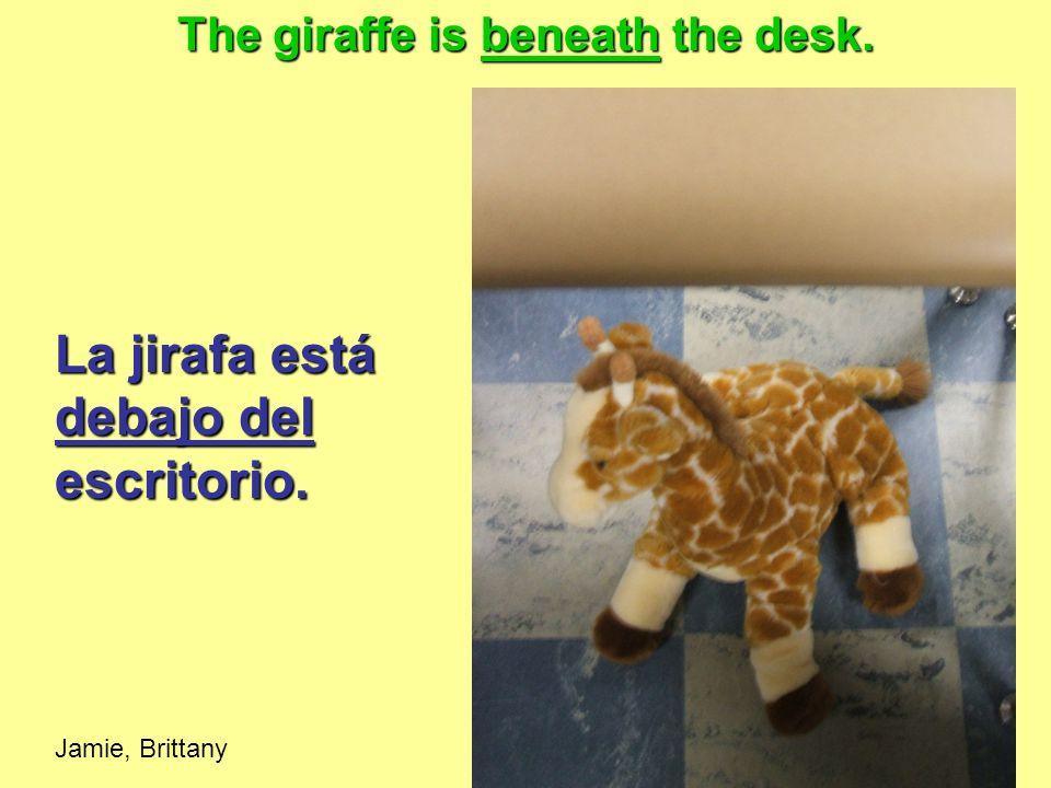 La jirafa está debajo del escritorio. Jamie, Brittany The giraffe is beneath the desk.