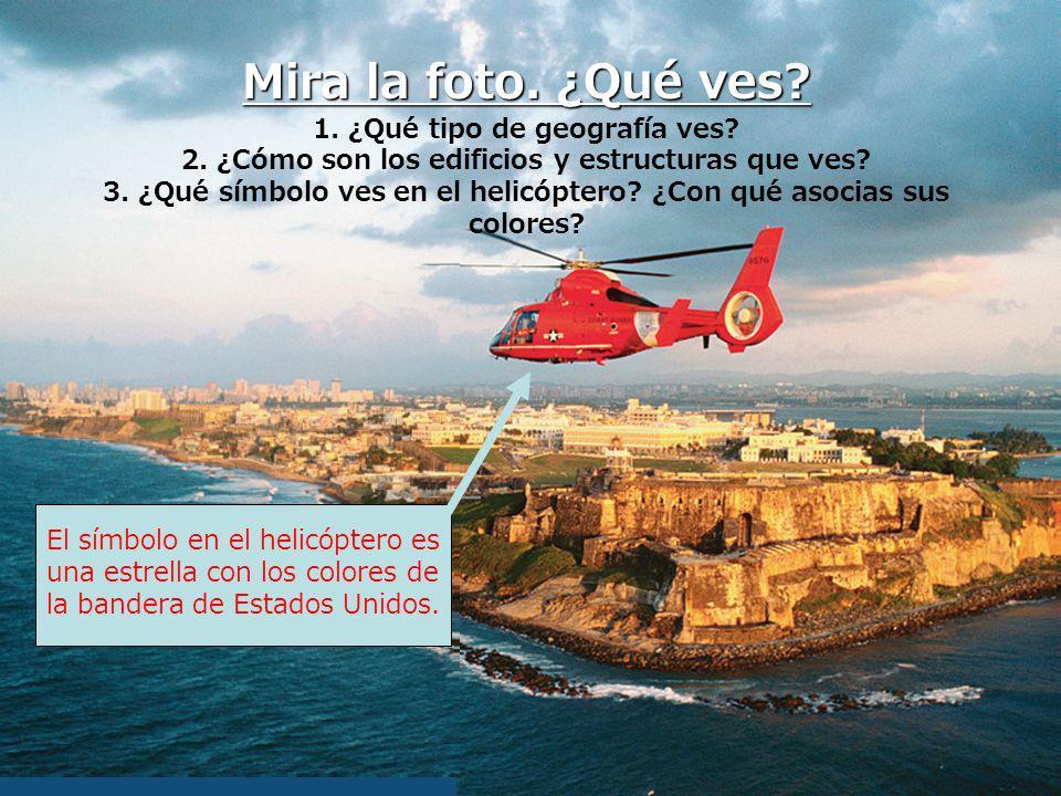 Mira la foto. ¿Qué ves? 1. ¿Qué tipo de geografía ves? 2. ¿Cómo son los edificios y estructuras que ves? 3. ¿Qué símbolo ves en el helicóptero? ¿Con q